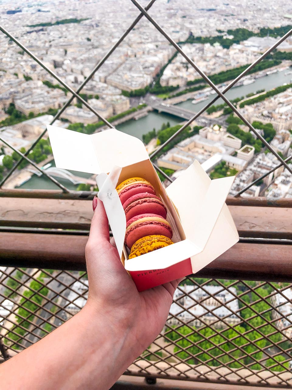 A woman's hand holding up a box of Pierre Hermé macarons at the top of the Eiffel Tower with the panorama of Paris visible in the background