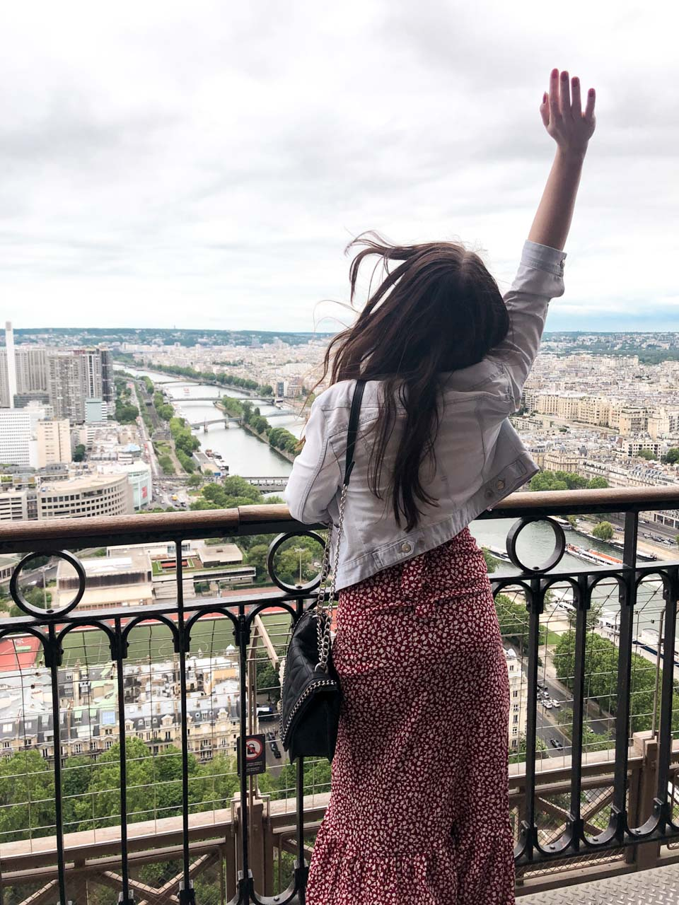 A dark-haired woman in a light denim jacket and a white and red dress with her back turned to the camera throwing her right hand up in the air as she is standing on the observation deck on the 2nd floor of the Eiffel Tower in Paris, France