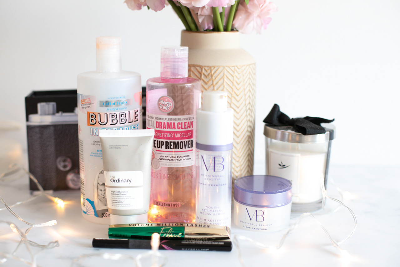 Empty beauty products from Soap & Glory, The Ordinary, Meaningful Beauty, L'Oreal and Maybelline on a marble desk in front of a vase with pink peonies