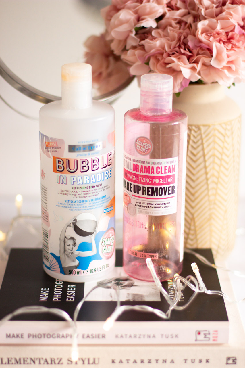 A close-up shot of empty bottles of the Soap & Glory Bubble in Paradise shower gel and Total Drama Clean make up remover placed on a stack of books on a marble desk
