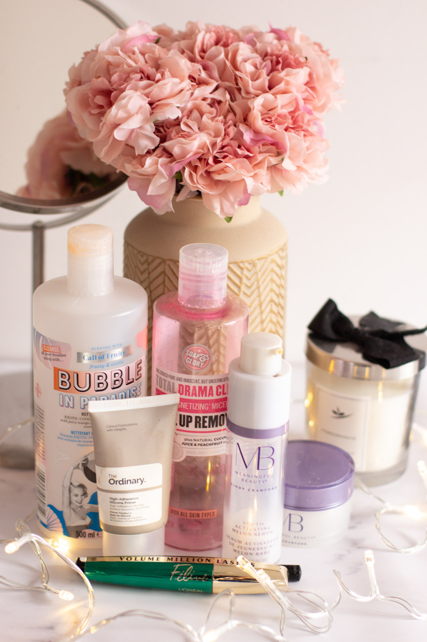 Empty beauty products from Soap & Glory, The Ordinary, Meaningful Beauty, L'Oreal and Maybelline on a marble desk in front of a vase with pink peonies and a makeup mirror