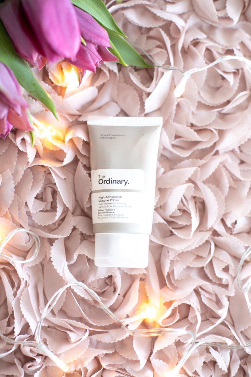 A tube of The Ordinary High-Adherence Silicone Primer against a pink backdrop